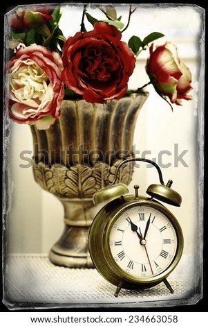 classic clock  watch in bright colorful retro interior behind red flowers - stock photo