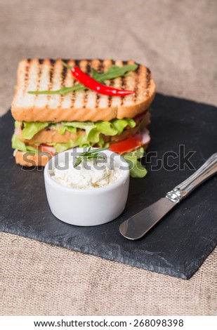 Classic club sandwich with bacon and vegetables on black plate - stock photo