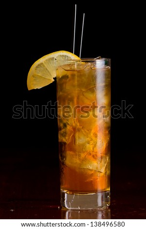 classic cocktail long island iced tea served on a bar and garnished with a lemon slice - stock photo