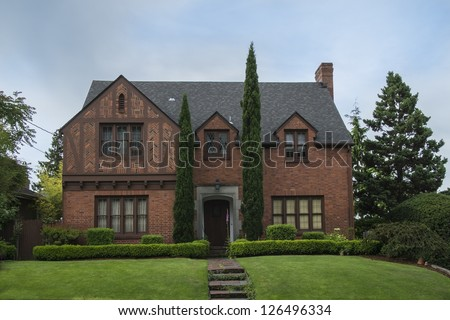 Classic colonial brick house with green lawn - stock photo