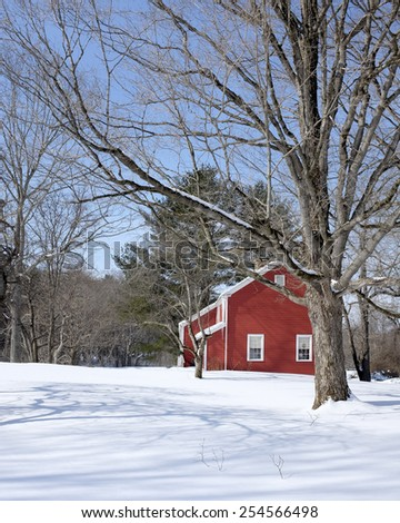 Classic colonial Vermont red home in winter with snow. - stock photo