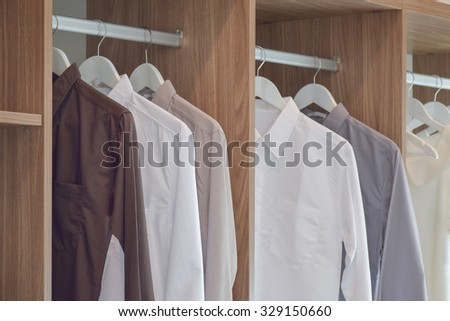 Classic color shirts hanging in wooden wardrobe