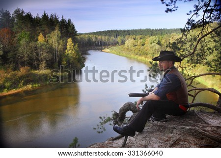 classic cowboy in traditional outfit in a natural scenery