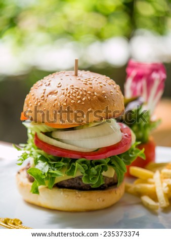 Classic deluxe cheeseburger with lettuce, onions, tomato and pickles on a sesame seed bun. Macro with shallow dof. - stock photo