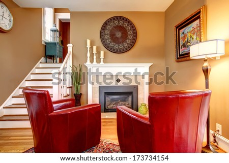 Classic designed family room with comfortable red chairs, light tones fireplace, hardwood floor and beige walls - stock photo