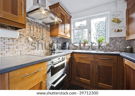 classic domestic kitchen with wooden counter and stone imitation worktop - stock photo