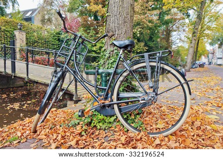 Classic Dutch bicycle parked against a treel in autumn, Gouda, The Netherlands - stock photo