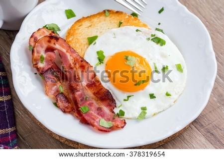 Classic English Breakfast, fried eggs, bacon, crunchy toast, tea, tasty dish - stock photo
