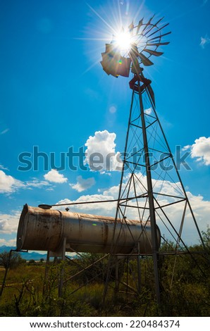 Classic Farm Windmill silhouetted with the Sun. - stock photo