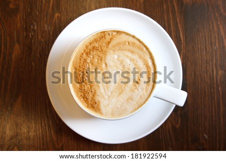 Classic foamy cappuccino in on a dark grained wood table. Detail. From above. - stock photo