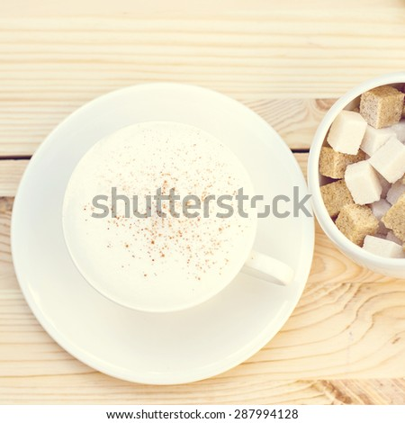 Classic foamy cappuccino in on a  wood table. Detail. From above. A cup of cappuccino - stock photo