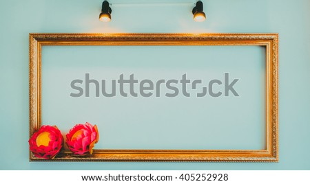 Classic golden vintage frame with blank space, spotlights and flower decor.  - stock photo