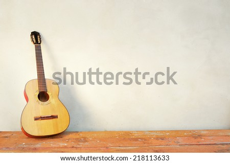 classic guitar with shadow in front of a white wall