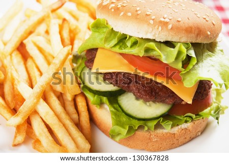 Classic hamburger with french fried, cheese, tomato and lettuce - stock photo