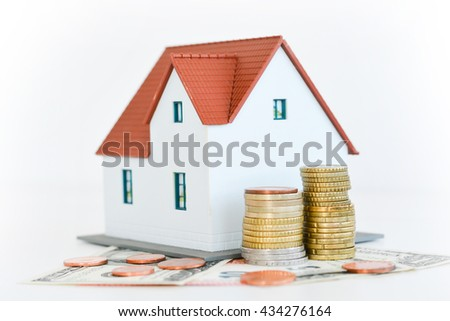 Classic home model with pile of coins isolated on white background