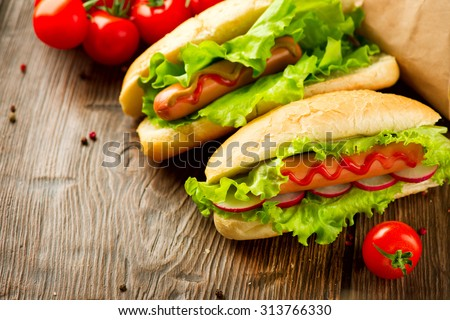 Classic Hot dogs close-up. Big Grilled hot dog with sausage, lettuce and radish served with ketchup sauce on dark wooden table. Homemade tasty hotdog meal. Food concept. Sandwich - stock photo
