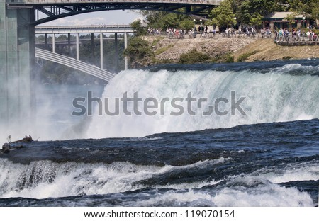 Classic image of Niagara Falls taken from Goat Island on the New York Side of the Niagara River. The image shows water rushing over the American Falls; the Observation Deck is visible in distance. - stock photo