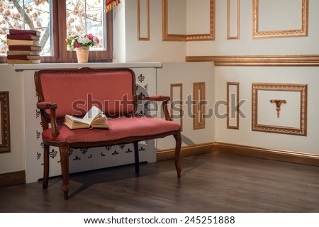 Classic interior design. Elegant interior in red and golden colors with a barocco couch with an open book standing against the window decorated with beautiful curtains and books on the window sill - stock photo