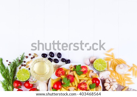 Classic Italian food - pasta with mushrooms, tomatoes, olives  and other ingredients on a wooden background - stock photo