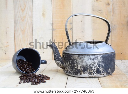 Classic kettle with coffee bean and black cup on wood board