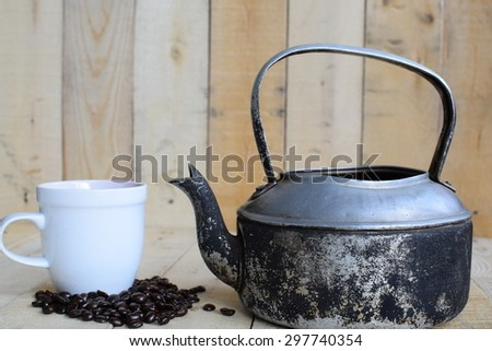 Classic kettle with coffee beans and white cup on wood board