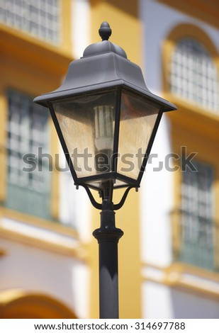 Classic lamp light over a yellow and white building facade. Vertical - stock photo