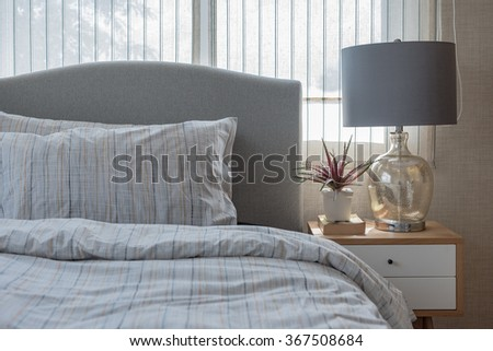 classic lamp style with vase of plant on wooden table in bedroom design