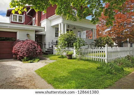Classic large craftsman old American house exterior in red and white during spring.