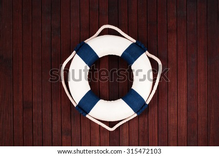 Classic lifebuoy on a wooden planks background.