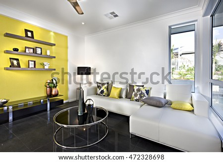 Classic living room with a sofa and pillows with reflective tile floor and round table, there is a rack on the yellow wall and some windows on the white walls