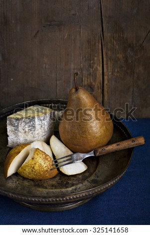 Classic low key still life with Blue cheese with pears on an old fashioned plate against deep blue table cloth and wooden wall. One pear is chopped in pieces and old fashioned fork pricks one piece.