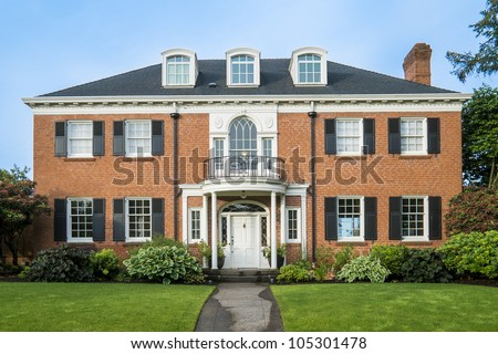 Classic luxurious red brick house with green lawn - stock photo