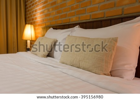Classic luxury bedroom with wall, pillows and lamps. - stock photo