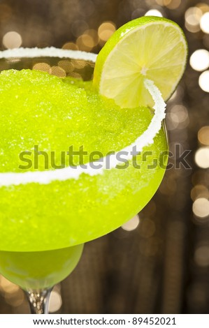 Classic margarita cocktail in front of different colored backgrounds - stock photo