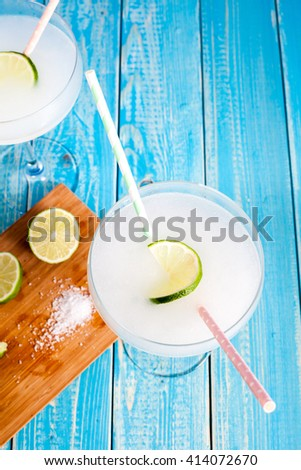 Classic Margarita Cocktail in margarita glass served with lime on aqua wood table. Cocktail ingredients: tequila, lime juice, orange liquor, ice and sea salt - stock photo