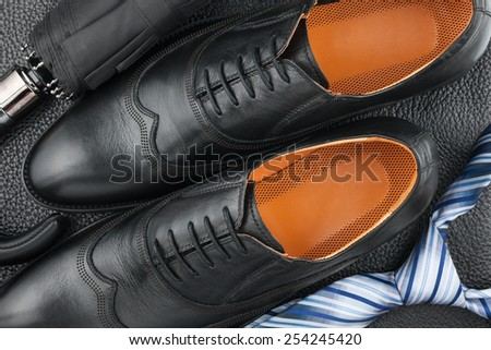 Classic men's shoes, tie, umbrella on the black leather, can be used as background - stock photo