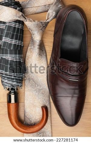 Classic men's shoes, tie, umbrella on the wooden floor, can be used as background