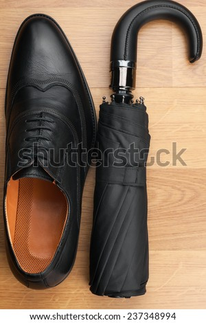 Classic mens shoes and  umbrella  on the wooden floor, can be used as background