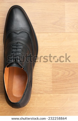 Classic mens shoes stand on the wooden floor, with place for your text - stock photo