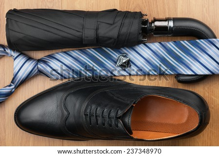 Classic mens shoes, tie, umbrella,cufflinks on the wooden floor, can be used as background - stock photo