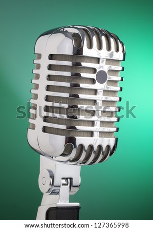 Classic microphone isolated on green background - stock photo