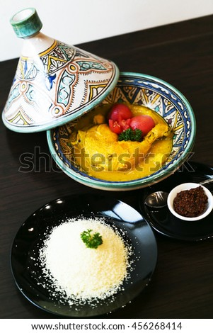 Classic Moroccan chicken tagine with Couscous on the wooden table - stock photo
