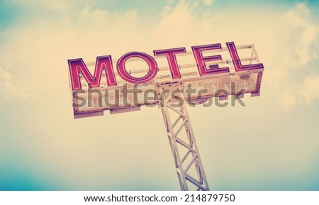 Classic motel sign against blue sky with Instagram style filter - stock photo