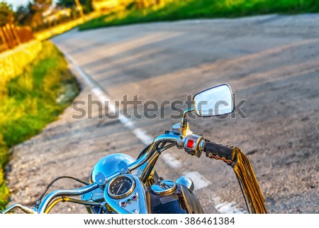 classic motorcycle on the edge of the road at sunset - stock photo