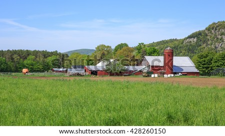 Classic New England family farm with red wooden barn, silo and buildings.