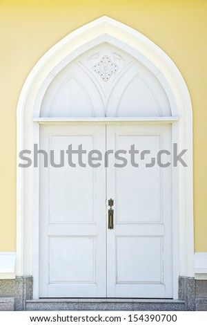 Classic old door on yellow wall. - stock photo
