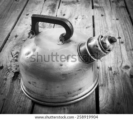 Classic old metal tea kettle in real vintage style on a wooden table in black and white - stock photo