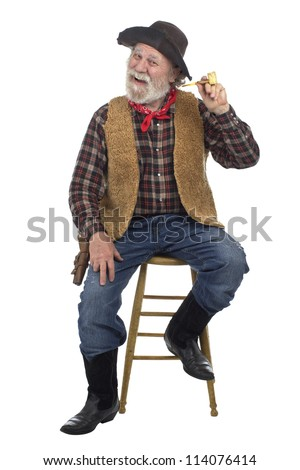 Classic Old West style cheerful cowboy with felt hat, grey whiskers, revolver. He holds corn cob pipe and sits on stool. Isolated on white, vertical, copy space. - stock photo