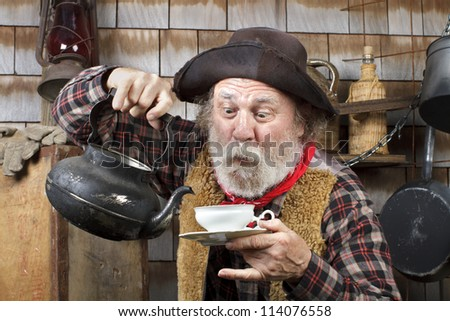 Classic Old West style cowboy cook with felt hat, grey whiskers, red bandanna. He is ready to pour tea into a white china tea cup. - stock photo