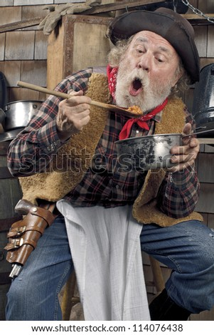 Classic Old West style cowboy with felt hat, grey whiskers, red bandana. He sits on a stool eating beans from a saucepan. Camp cookware and wood shingles in background. - stock photo